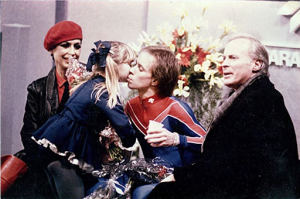 Harris (far left) sitting in the 1984 Olympic Kiss & Cry with Scott Hamilton & coach Don Laws.